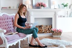 Portrait of gorgeous blonde woman with laptop working at home. Woman sitting on pink sofa in light luxury interior with stock image