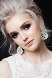 Portrait of gorgeous blonde woman with stylish haircut, perfect evening make up, long eyelashes and pure skin. Bride wearing lace Stock Photos