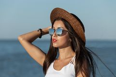 Portrait of a gorgeous brunette girl with long hair and red lipstick in white dress, sunglasses and brown hat near the stock image