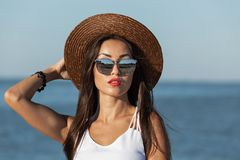 Portrait of a gorgeous brunette girl with long hair and red lipstick in white dress, sunglasses and brown hat near the royalty free stock image