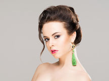 Portrait of gorgeous brunette wearing luxury earrings over isola. Ted background Stock Photo