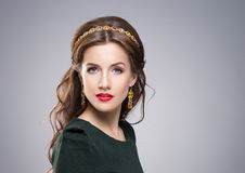 Portrait of gorgeous brunette wearing luxury golden coronet and earrings Royalty Free Stock Photography