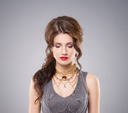 Portrait of gorgeous brunette wearing luxury golden coronet and earrings.  Royalty Free Stock Photography