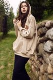 Gorgeous brunette woman in fashion hoodie in the garden alley stock photography