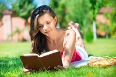 Portrait of a gorgeous brunette woman reading a book Stock Photos