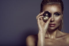Portrait of gorgeous chic blond woman with wet hair, glittering artistic make-up and bronze skin holding a big shining gem Stock Photo