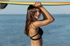 Portrait of gorgeous dark-haired girl in a black bra holds a surfboard over her head near the sea. royalty free stock photo