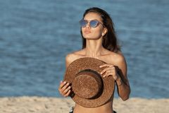 Portrait of gorgeous dark-haired girl in sunglasses holding a hat on her chest near the sea on a sunny day royalty free stock images