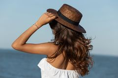 Portrait of gorgeous dark-haired girl in white dress and hat near the sea on a sunny day. Back view. royalty free stock photos