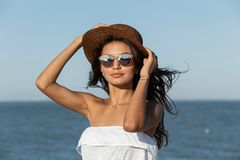 Portrait of gorgeous dark-haired girl in white dress, sunglasses and hat near the sea on a sunny day. royalty free stock photos