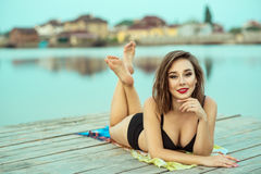 Portrait of gorgeous dark-haired smiling girl with red lips in black swimming suit lying on the wooden pier at the lake Royalty Free Stock Images