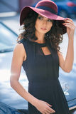 Portrait of gorgeous elegant brunette woman in a hat near black car Royalty Free Stock Photos