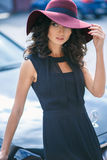 Portrait of gorgeous elegant brunette woman in a hat near black car Royalty Free Stock Images