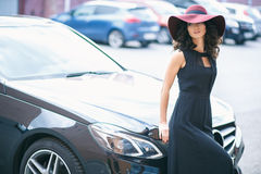 Portrait of gorgeous elegant brunette woman in a hat near black car Royalty Free Stock Photography