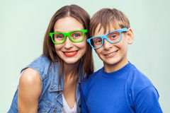 Portrait of gorgeous freckled brother and sister in casual t shirts wearing trendy glasses and posing over light blue background Royalty Free Stock Photo