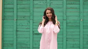 Portrait of a gorgeous girl against a green wall. Portrait of a gorgeous girl in a pink dress on a background of a green wooden wall. Slow motion stock video footage