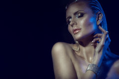 Portrait of gorgeous glam blond woman with wet hair, artistic glittering make-up and naked shoulders touching her neck royalty free stock photo