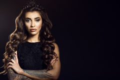 Portrait of gorgeous glam tattooed model with long wavy silky hair and provocative make up wearing lace dress and jewel crown. Isolated on black background Stock Photography
