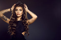 Portrait of gorgeous glam tattooed model with long wavy silky shiny hair and provocative make up putting up a jewel crown royalty free stock images