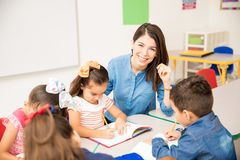 Beautiful preschool teacher during class. Portrait of a gorgeous Hispanic preschool teacher teaching her students in a classroom stock images
