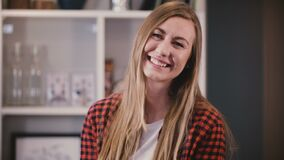 Portrait of gorgeous lady posing at camera. Pretty young blonde girl with long hair smiling happily. Positive emotion 4K. Portrait of gorgeous lady posing at stock footage