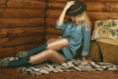 Portrait of gorgeous long-legged girl wearing jeans shorts, shirt, suede boots with floral embroidery and stetson felt hat Stock Photos