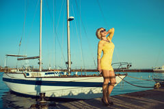 Portrait of gorgeous middle-aged blond smiling woman wearing yellow tight-fitted lace mini dress and sunglasses enjoying sunshine Stock Image