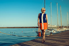 Portrait of gorgeous middle-aged blond woman in trendy dress and sunglasses walking along the pier holding an orange shoulder bag Stock Photo