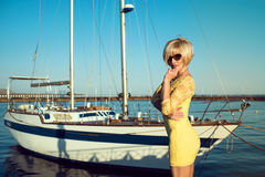 Portrait of gorgeous middle-aged blond woman wearing yellow tight-fitted lace mini dress and sunglasses standing on the yacht pier royalty free stock image