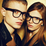Portrait of gorgeous red-haired fashion twins in black clothes. Wearing trendy glasses and posing over golden background together. Perfect hair. Natural make-up Royalty Free Stock Photos