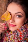 Portrait of a gorgeous romantic young woman holding an autumn leaf in front of her right eye, smiling subtly at the