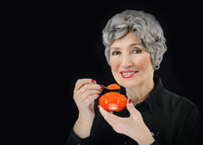 Portrait of gorgeous senior woman eating red caviar Royalty Free Stock Images