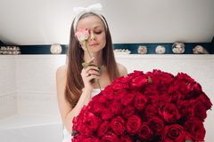 Attractive woman in towel and headband with bouquet of red roses. stock images