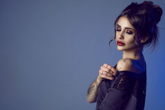 Portrait of gorgeous sexy dark-haired tattooed young woman with provocative make-up taking a black silk peignoir off her shoulder Royalty Free Stock Image