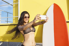 Portrait of a gorgeous smiling surfer women in bikini making self portrait with mobile phone camera Royalty Free Stock Photos