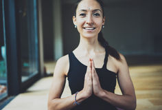 Portrait of gorgeous, smiling young woman practicing yoga indoor. Beautiful girl practice meditation asana in class Royalty Free Stock Photography