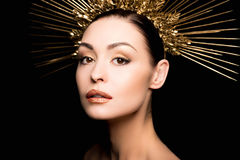 Portrait of gorgeous woman in golden headpiece looking at camera Stock Images