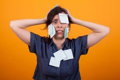 Portrait of gorgeous woman stressed with work over yellow background in studio. Blue sticky notes. Overwhelmed woman royalty free stock images