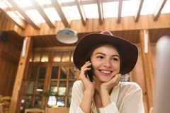 Portrait of gorgeous woman wearing hat speaking on smartphone royalty free stock photo