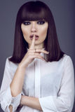 Portrait of gorgeous young dark-haired woman with provocative make up and expressive eyes looking straight with hush gesture. Portrait of gorgeous young dark stock photography