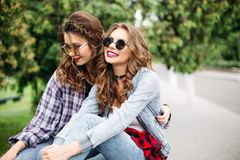 Couple of beautiful trendy teen girls in sunglasses in park. Portrait of gorgeous young girls with brunette and blonde hair in hairstyles wearing fashionable royalty free stock images