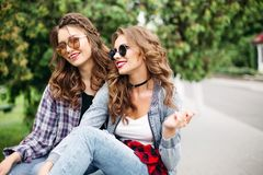 Couple of beautiful trendy teen girls in sunglasses in park. Portrait of gorgeous young girls with brunette and blonde hair in hairstyles wearing fashionable stock photos