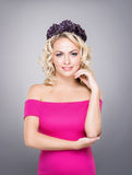 Portrait of gorgeous, young lady wearing pink dress and purple wreath. Over grey background Stock Image