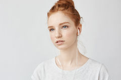 Portrait of gorgeous young redhead girl listening to streaming music in headphones concentrated on her bright thoughts Royalty Free Stock Image