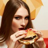 Portrait of beautiful woman eating burger. Portrait of gorgeous young woman with closed eyes and red lips holding tasty cheeseburger and biting it. Attractive Royalty Free Stock Photography
