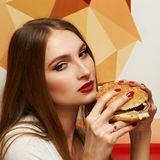 Portrait of beautiful woman eating burger. Portrait of gorgeous young woman with closed eyes and red lips holding tasty cheeseburger and biting it. Attractive Royalty Free Stock Photos