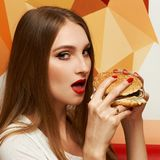 Portrait of beautiful woman eating burger. Portrait of gorgeous young woman with closed eyes and red lips holding tasty cheeseburger and biting it. Attractive Stock Photo