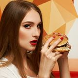Portrait of beautiful woman eating burger. Portrait of gorgeous young woman with closed eyes and red lips holding tasty cheeseburger and biting it. Attractive Royalty Free Stock Photo