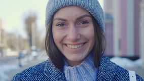 Portrait of gorgeous young woman in knit cap outdoor. Attractive young lady is smilig on city street. Portrait of gorgeous young woman in knit cap outdoor stock video