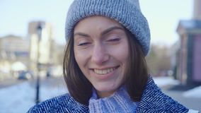 Portrait of gorgeous young woman in knit cap outdoor. Attractive young lady is smilig on city street. Portrait of gorgeous young woman in knit cap outdoor stock video footage